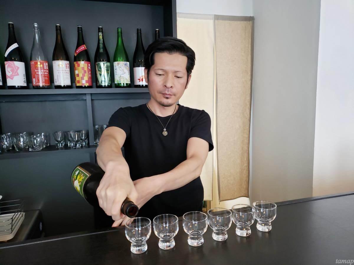 日本酒バー花あかりの店内で荒井さんが日本酒を注いでいるところ